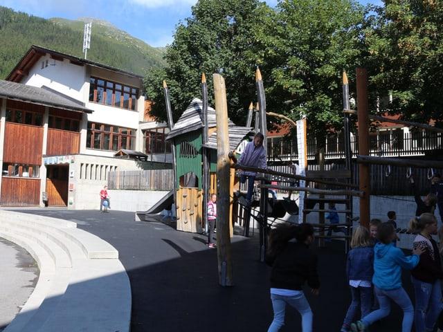 Spielturm mit Kindern, im Hintergrund ein Teil des Schulhauses.