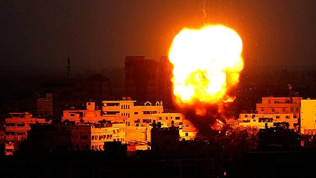 Ein gelber Feuerball steigt in der Nacht über Gaza City auf.