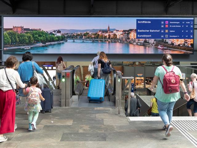 Menschen in der Bahnhofspassarelle vor länglicher Anzeigetafel