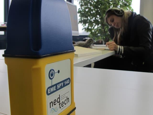 Ein kleines Messgerät (gelber Kasten mit blauem Deckel) auf einem Pult neben einem Arbeitsplatz.