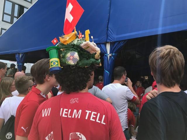 Ein Fussballfan mit einem speziell auffälligen Hut mit Schweizerkreuz, Käse und Brasilienfahne