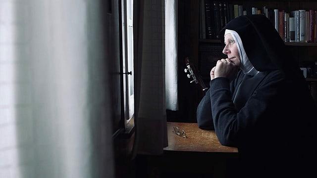 Eine Nonne sitzt an einem Tisch und schaut durchs Fenster