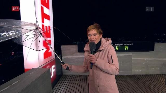 Sandra Boner hält einen zerstörten Schirm auf dem Meteodach in der Hand.