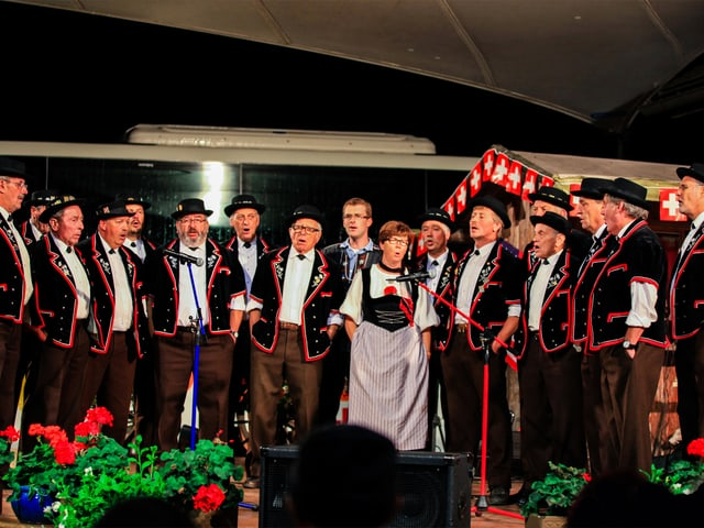 Eine Frau und 19 Männer im Halbkreis auf einer Bühne während eines Auftritts.