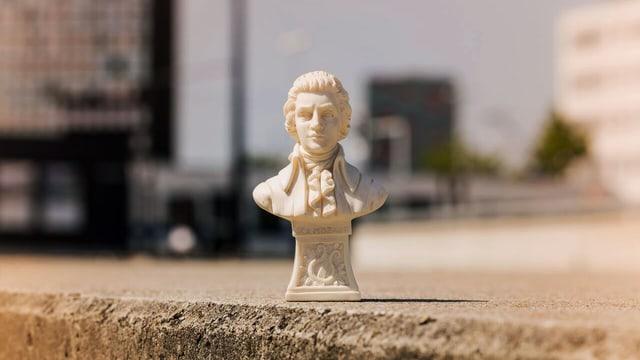 Eine  fausthohe Mozartfigur auf einer Mauer platziert.
