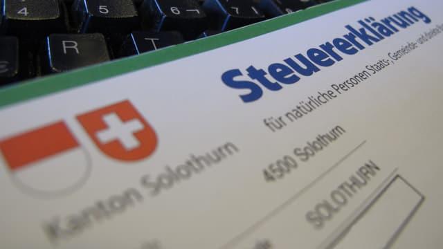 Steuererklärung aus dem Kanton Solothurn auf einer Computer-Tastatur