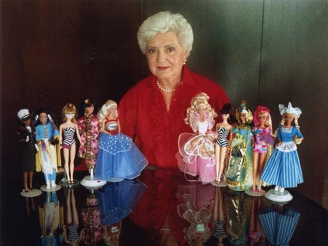 Eine Frau an einem Tisch, auf dem mehrere kleine Puppen stehen.