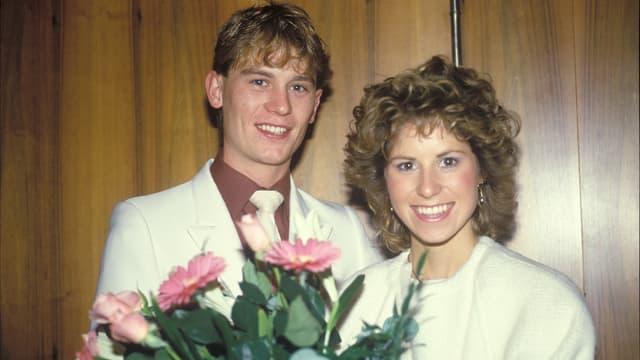 ein junges Ehepaar lächelt in die Kamera und hält einen Blumenstrauss