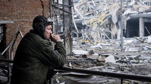 Soldat raucht, dahinter zerstörte Gebäude