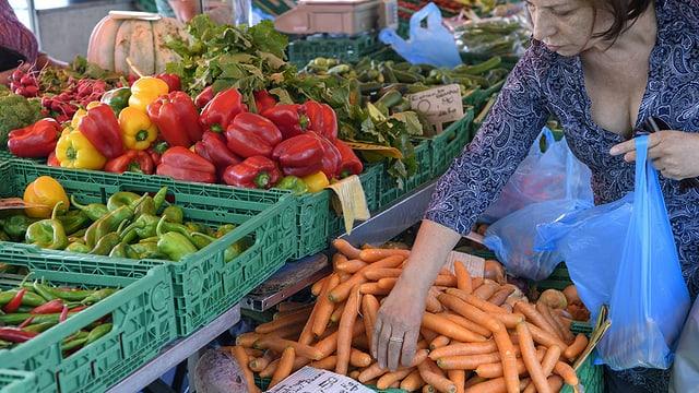 martgà da verdura, ina dunna pachetescha rebas en in satget