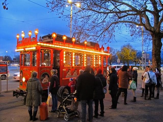 Das Märchentram steht in der Tramschleife des Bellevues, davor stehen Eltern mit Kinderwagen.