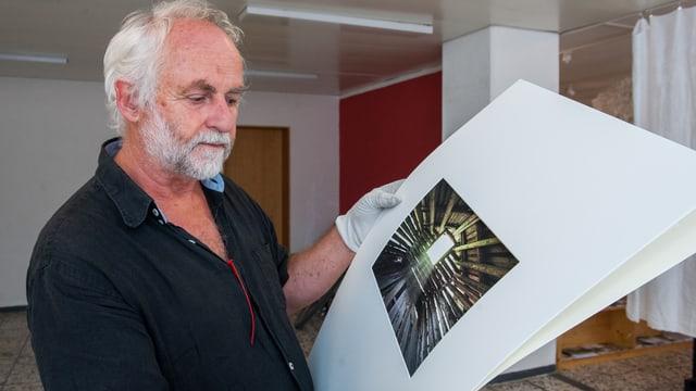 Fridolin Walcher vid preparar las fotografias per l'exposiziun a Glion.