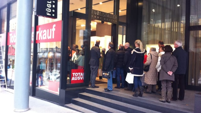 Leute stehen vor der Türe des Ladens und warten.