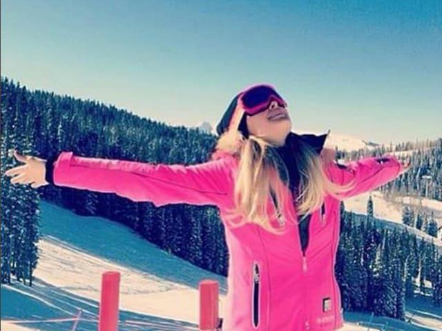 Paris Hilton mit Skibrille vor verschneiter Berglandschaft blickt die Hände ausgestreckt in den Himmel.