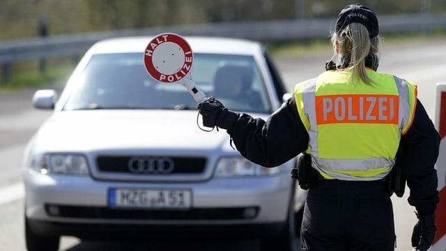 Polizistin hält Auto auf.
