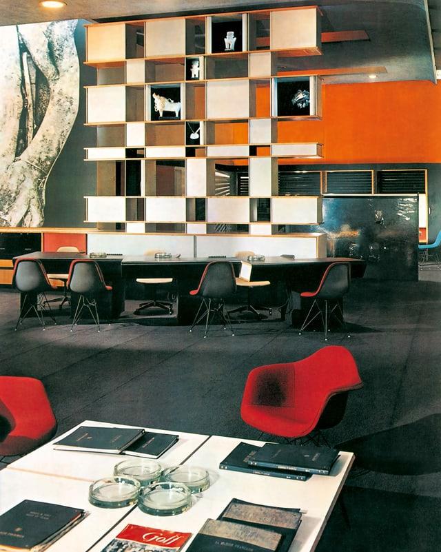 Empfangsbereich der Büros von Air France in London, um 1960. Ein weisses Rregal, im Vordergrund sind zwei rote Eams-Stühle.