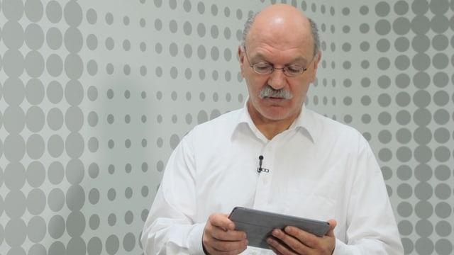 Köbi Gantenbein hält ein Tablet in den Händen