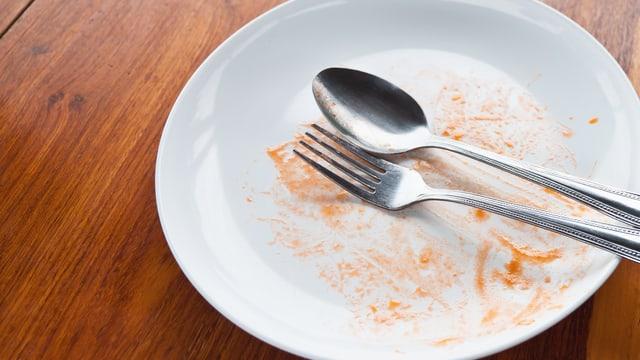 Leerer Teller mit Besteck und Spuren von Tomatensauce