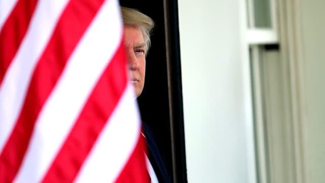 Trump wird halb von einer US-Flagge verdeckt.