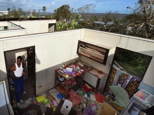 Ein Mann steht in seiner verwüsteten Wohnung ohne das Dach.
