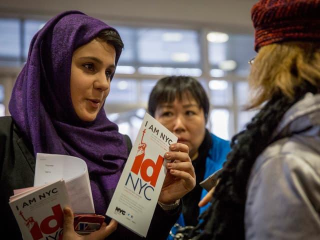 """Eine Frau mit Kopftuch verteilt Broschüren mit der Aufschrift """"IDNYC"""""""