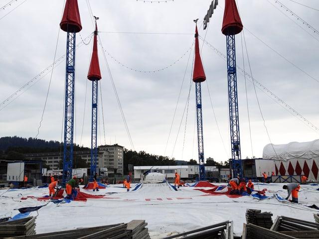 Arbeiter in orangen Gewändern bauen das Zelt des Zirkus Knie auf.