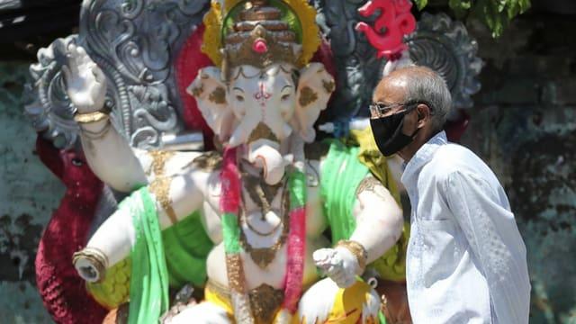 Ein Mann mit Maske vor einer Ganesha-Figur.