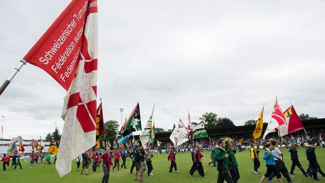 Fahnenschwinger laufen in einer Reihe durch ein offenes Stadion