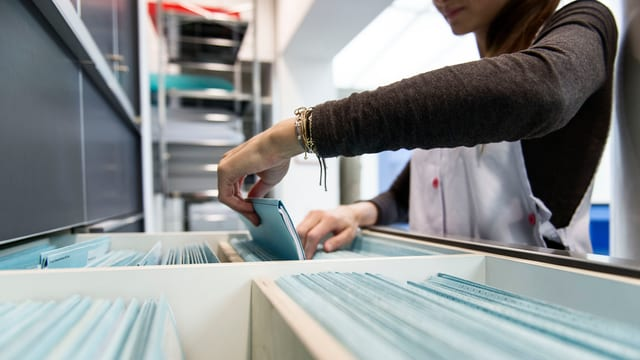 junge Frau wühlt in Schubalde mit Karteiblättern