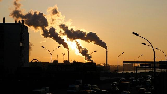 Rauchende Fabrikschlote, dahinter aufgehende Sonne