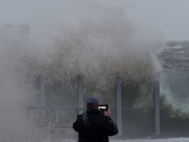 Hohe Welle trifft auf Küste, davor steht ein Mann, der fotografiert.