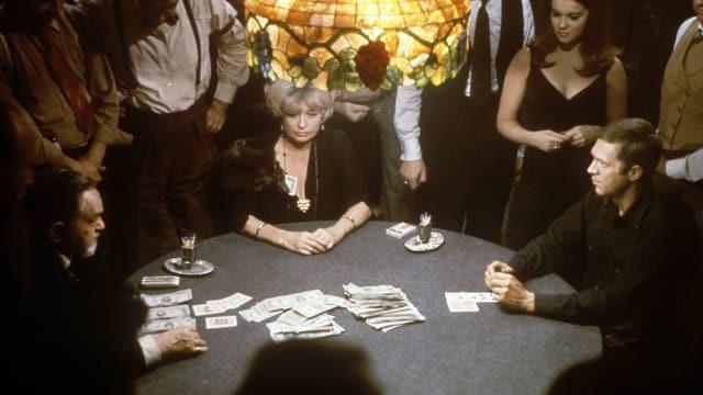 An einem runden Tisch spielen zwei Männer Poker.