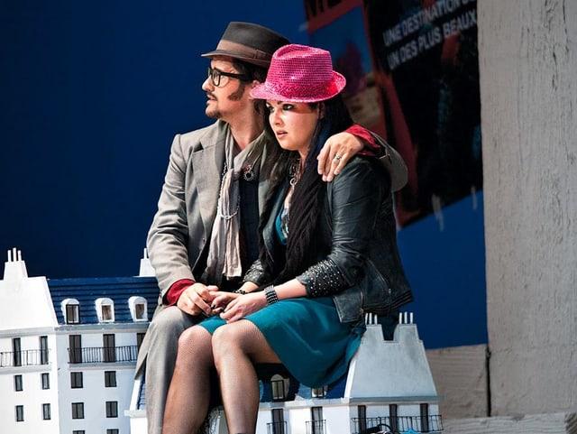 Ein Bühnenbild: Ein Mann umarmt eine Frau. Sie sitzen auf einem Haus, das so klein ist wie eine Bank.