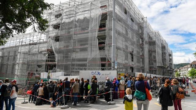 Hunderte Menschen stehen bei einer Baustelle für eine neue Wohnung an