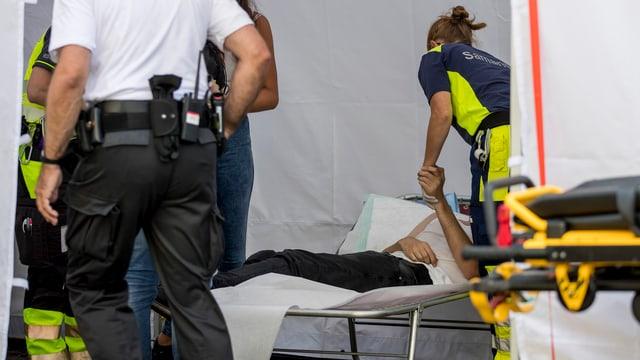 Ein Mann liegt in einem Sanitätszelt.
