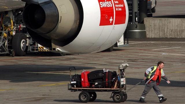 Mitarbeiter zieht Wagen mit Koffern.