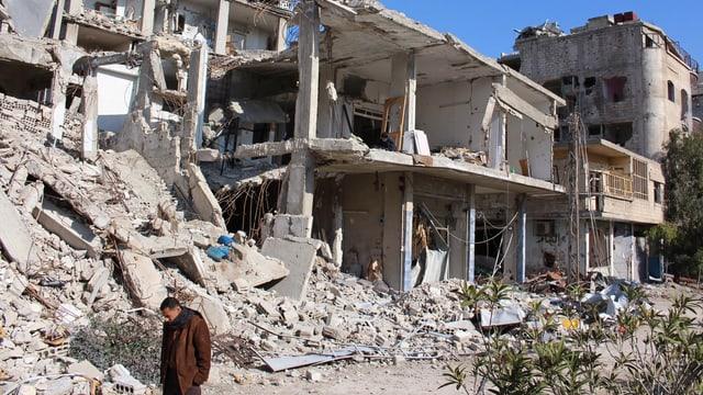 Zerbombte Häuser in einem Damaszener Vorort, davor ein Mann mit gesenktem Kopf.