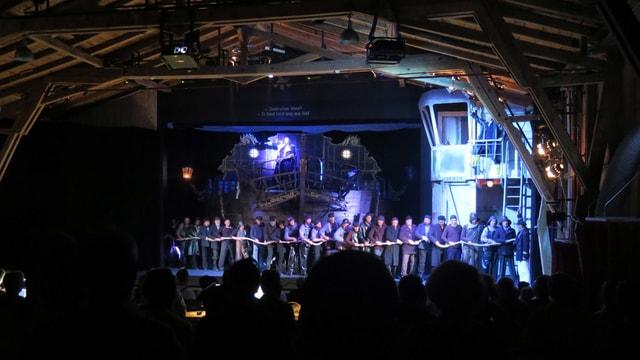 Chor aus Seemännern zieht an einem Seil, im Hintergrund das imposante Bühnenbild