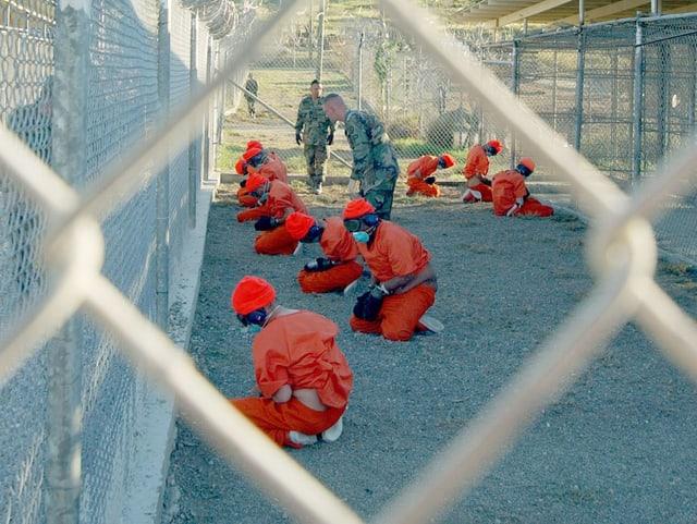 Häftlinge in Guantanamo. Vorne ist ein Zaun.