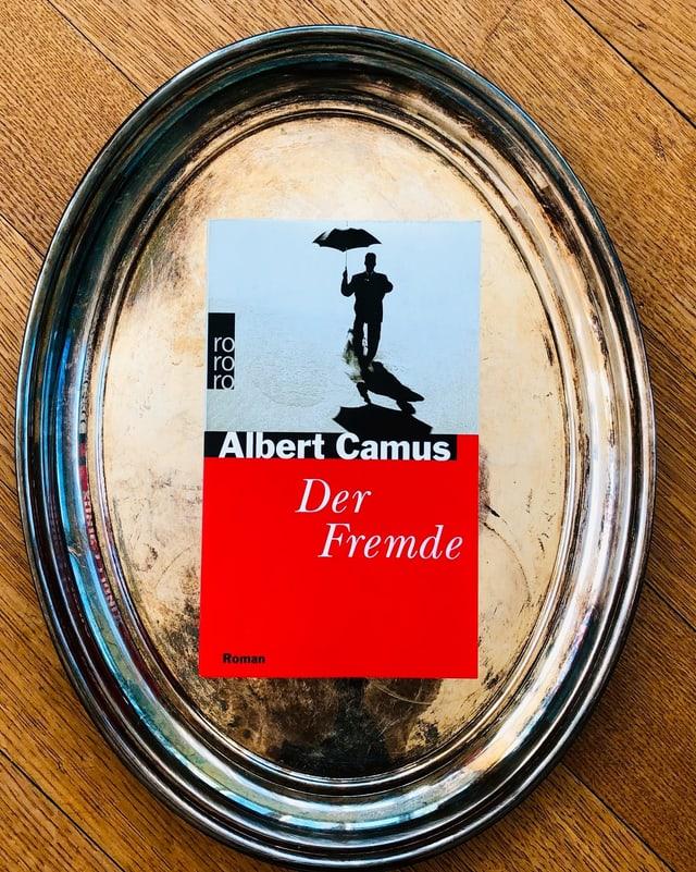 «Der Fremde» von Albert Camus liegt auf einem Silbertablett