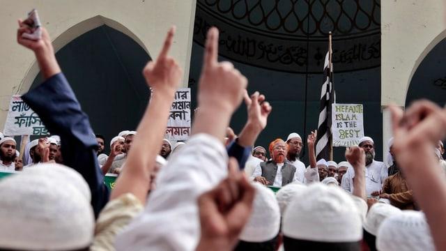 Kundgebung von Moslems in Bangladesch vor einer Moschee, einige halten eine Hand in die Luft.