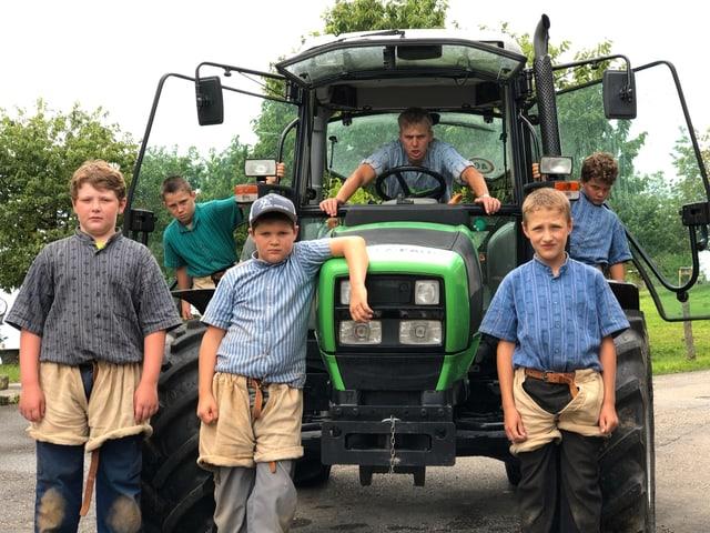 Fünf Buben und Moderator Reto Scherrer sitzen auf resp. stehen vor einem grünen Traktor.
