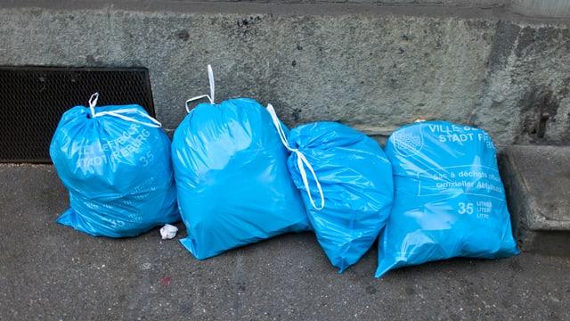 Blaue Abfallsäcke am Strassenrand.