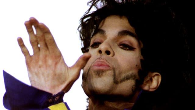 Ein Mann mit geschminkten Augen und besonderer Bartrasur wirft eine Kusshand.