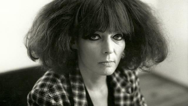 Schwarz-weiss Porträt der Autorin Gisela Eslner in kariertem Jacket und mit schulterlangem, stark toupiertem Haar.