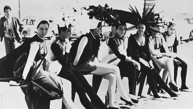 Eine Gruppe von Frauen in exzentrischen Kostümen sitzt auf einer Mauer.