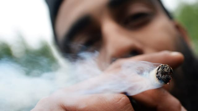 Nahaufnahme: Ein Mann zieht an einem Joint.