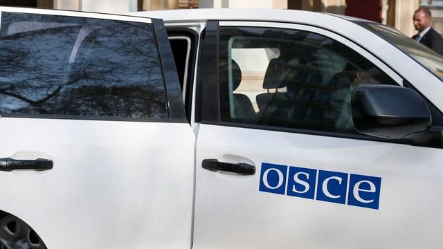 Weisses Auto der OSZE mit Schriftzug der Organisation auf der Vordertüre