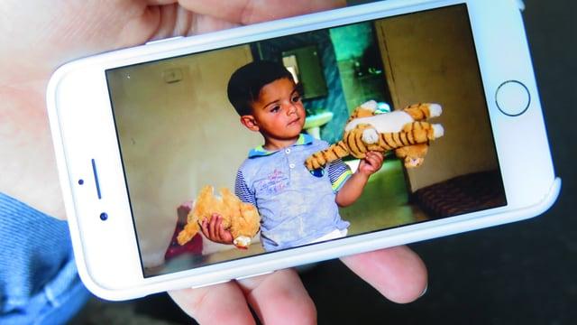 Eine Hand hält ein Smartphone. Auf dem Smartphone ist ein jordanischer Junge mit seinem Kuscheltieren zu sehen.