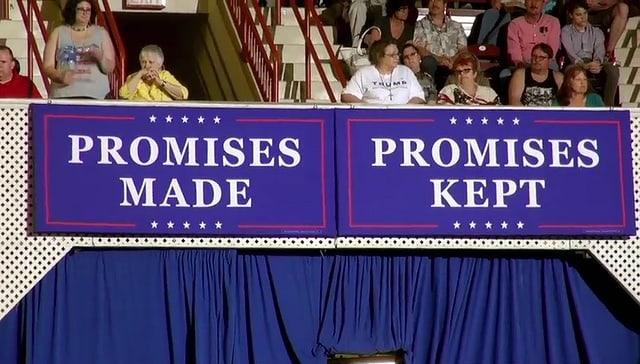 """Zwei Plakate, auf dem einen steht """"Verprechen gemacht*, auf dem anderen """"Versprechen gehalten"""""""